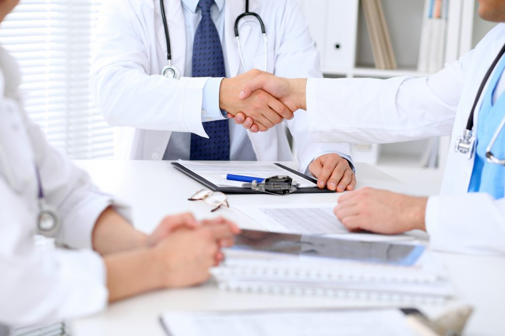 Two,Doctors,Shaking,Hands,To,Each,Other,Sitting,At,The